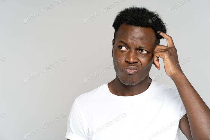 Unsure doubtful African man scratching head, looking left doubtfully, plans or reconsiders something