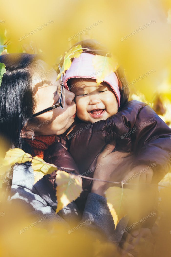 mother kissing baby in rompers in autumn park
