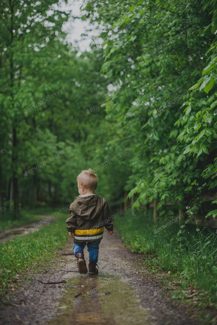 Little boy walking down a gravel road with trees