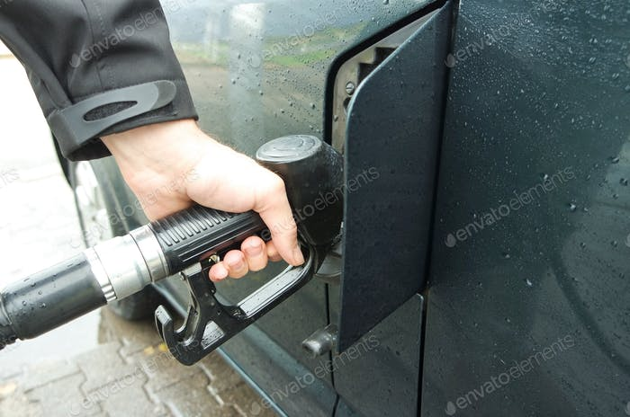 Refueling the van. Putting fuel in to the car. Rainy day and rain drops on the surface of the van.