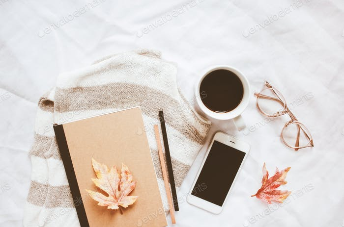 Autumn fashion style concept : sweater, notebook, coffee, smartphone, eyeglasses with maple leaves o