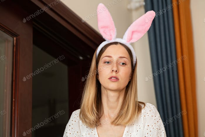 Young caucasian woman wearing rabbit bunny ears. Happy easter costume party at home