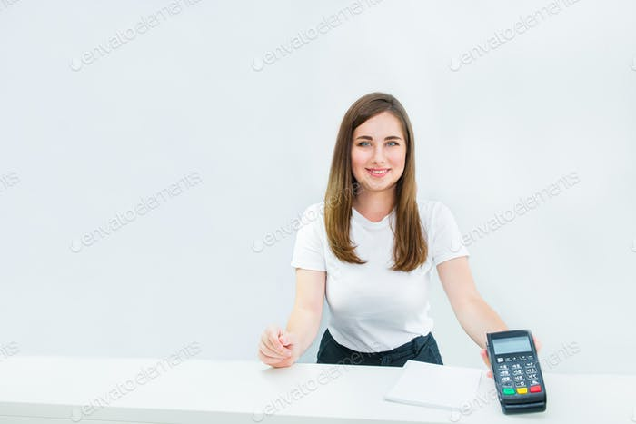 manager, seller holding payment terminal at reception desk. Contactless payment with nfc technology