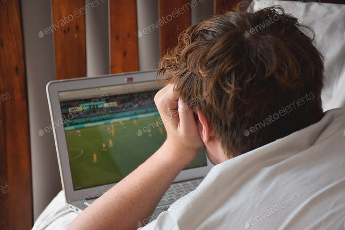 Young man laying on bed watching soccer game on laptop computer