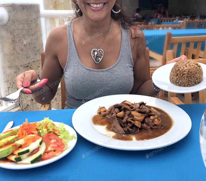 Happy Hispanic Latino woman ready to have a delicious tropical meal in a restaurant on the beach.