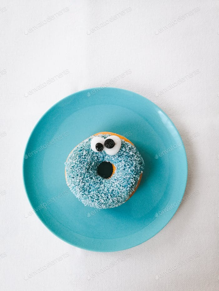 Turquoise colored  doughnut on turquoise colored plate.
