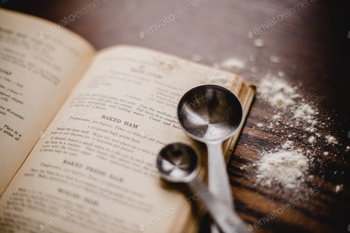 Close up of measuring spoons and cookbook as a kitchen vignette