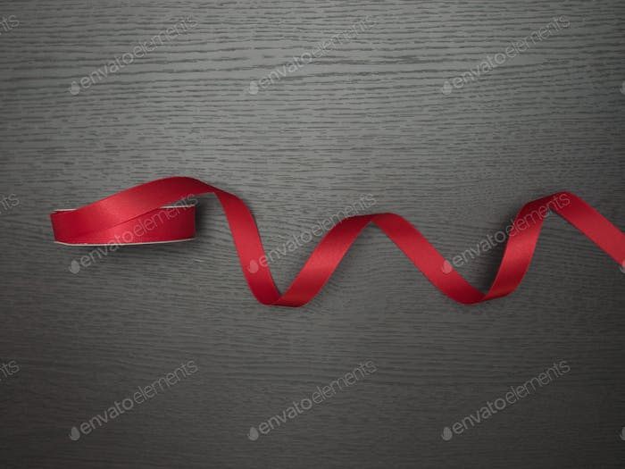 Single red object in dark wood background