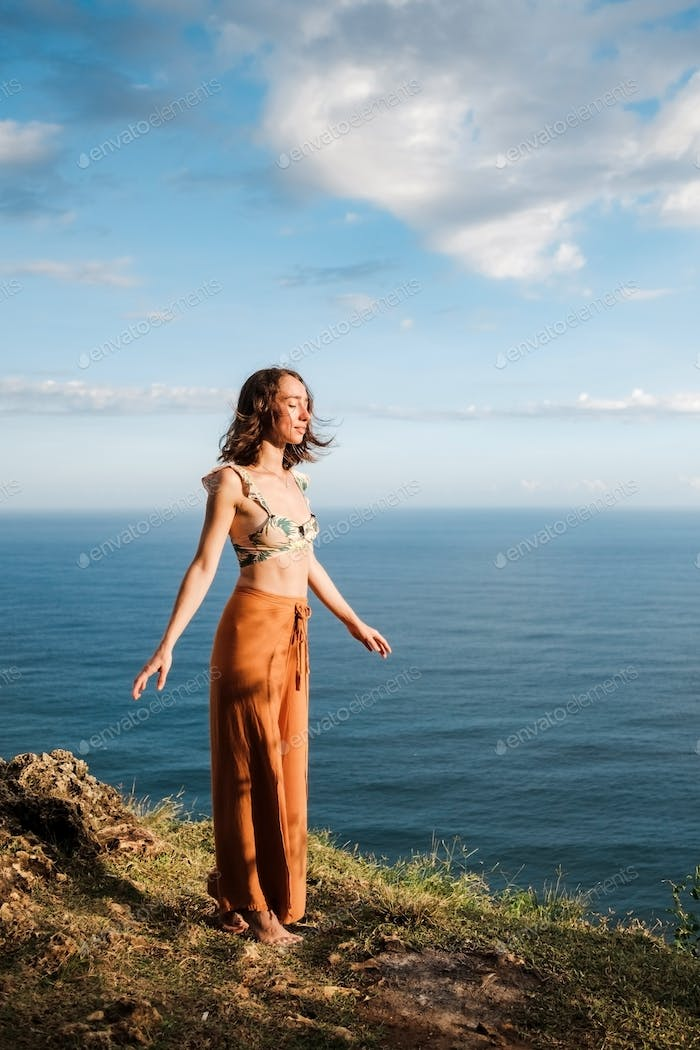 Young woman standing on cliffs edge with closed eyes near ocean