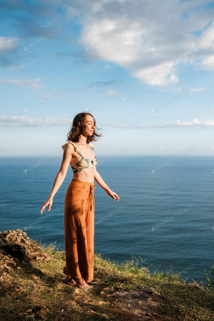 Thumbnail for Young woman standing on cliffs edge with closed eyes near ocean