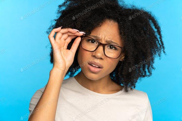 Skeptisches misstrauisches afrikanisch-amerikanisches Mädchen passt die Brille an und blickt verdächtig in die Kamera. Studio.