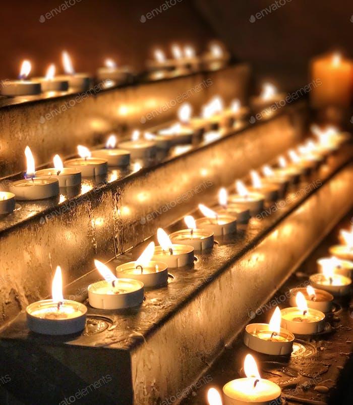 Reihen von Gebetskerzen werfen einen goldenen Schimmer in der Kathedrale
