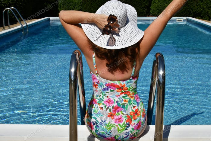 Middle-aged woman active Gen X full-figured female wearing swimsuit floppy hat with hand in the air
