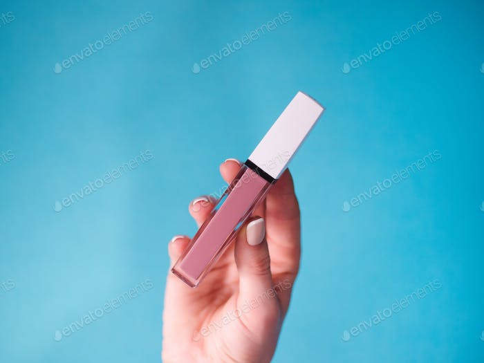 beautiful beige lip gloss in female hand isolated on blue background.