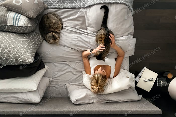 Woman cozy in bed with her kitties.