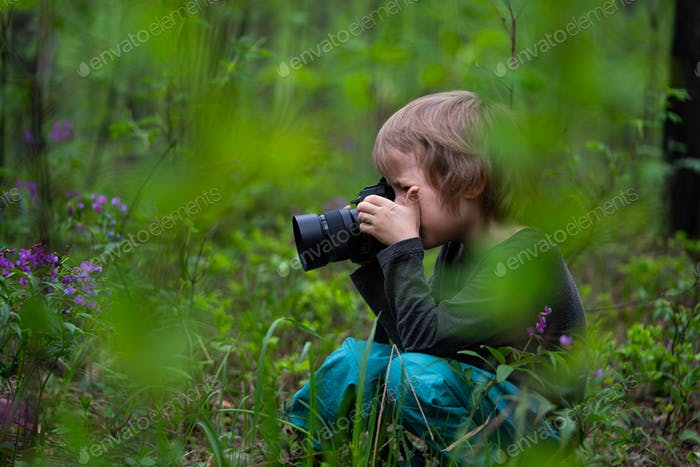 Little Boy using digital camera taking photo in the nature, hobbies or education concept