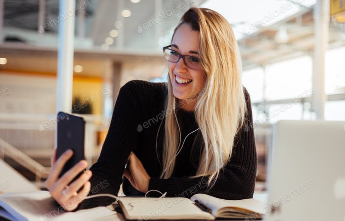 Happy smiling blonde girl facetime video calling at her desk while working and studying