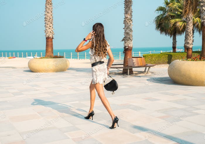 Young fashionable woman walking on heels at the beachside