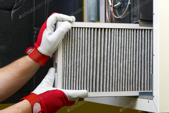 A mans hands that are replacing the condition air filter