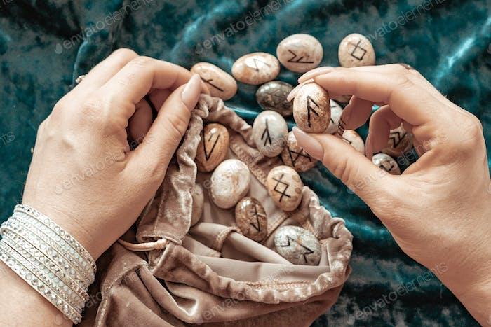 Steinrunen in den Händen einer jungen Frau und Kerzen auf blauem Samthintergrund