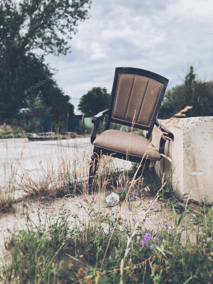 A discarded broken chair at the side of a road