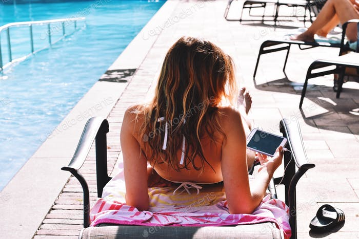 Young teenage girl in a bikini laying on a lounger by a swimming pool suntanning and watching videos