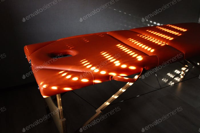Orange massage table with a patern of sunlight upon it , wellness and relaxation