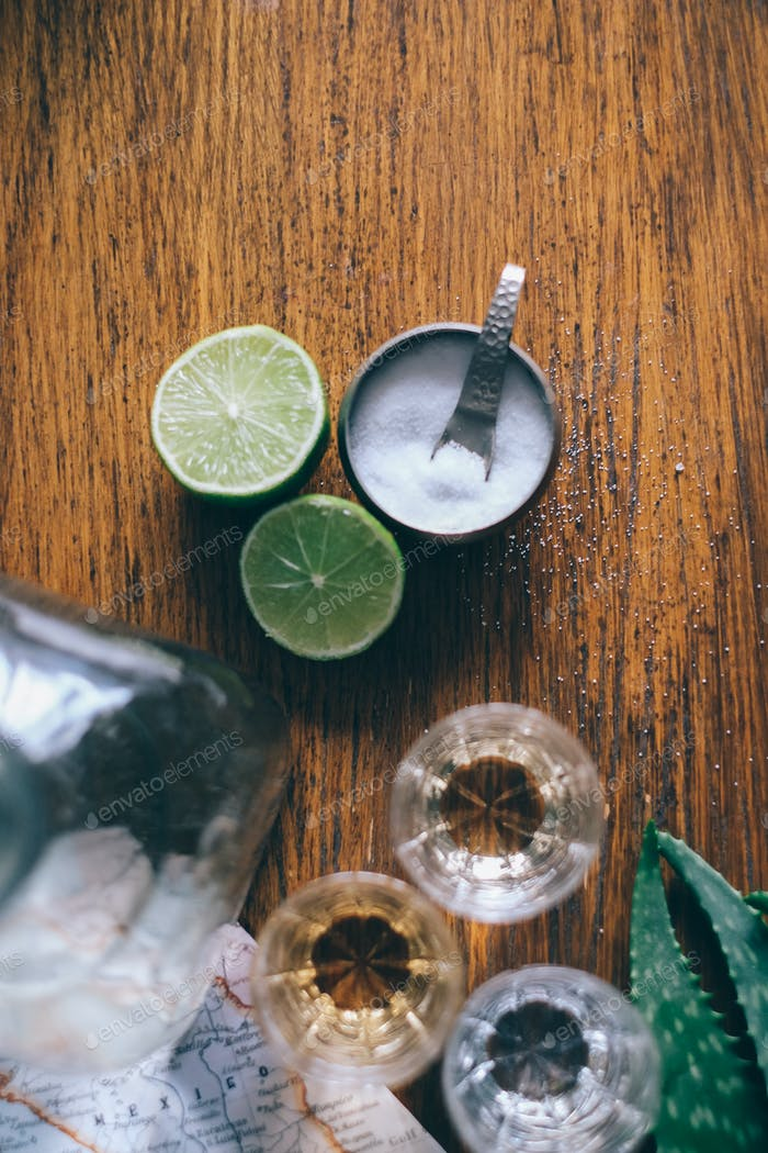 bottle and glasses with tequila and limes