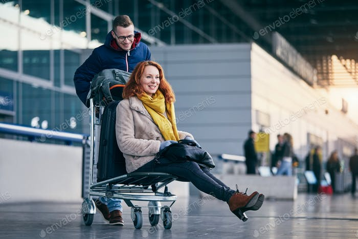 Cheerful couple travel together. Young man pushing woman on luggage trolley at airport.
