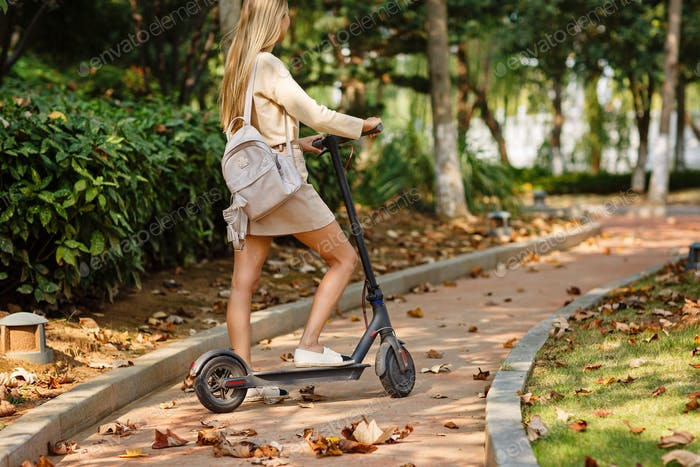 ⭐️⭐️⭐️ Nominated ⭐️⭐️⭐️   Woman riding on electric scooter in the park. Autumn, fall season, transp