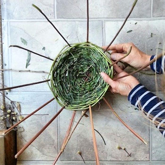 Directly above shot of hands weaving basket