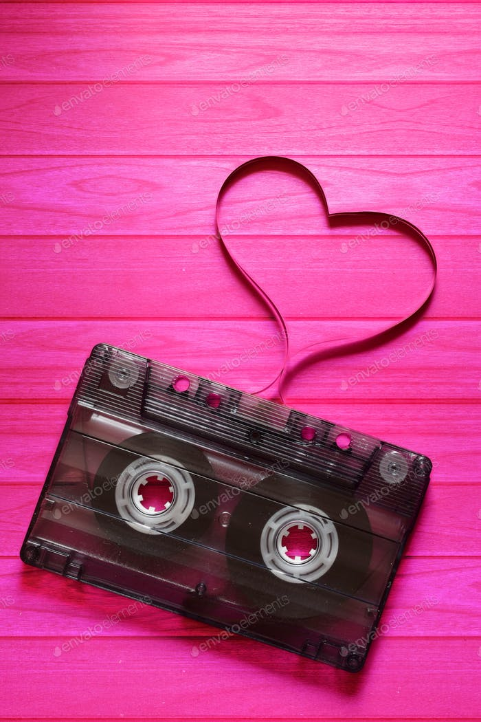 Old cassette on the pink background