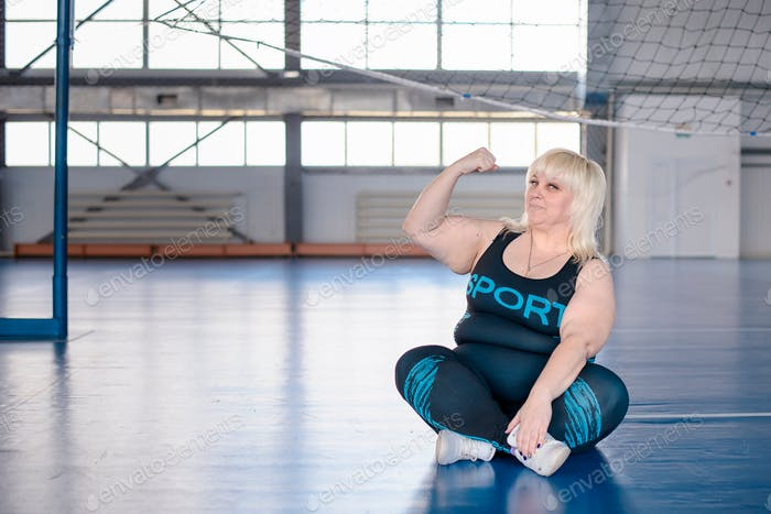 overweight woman sitting on mats in the gym