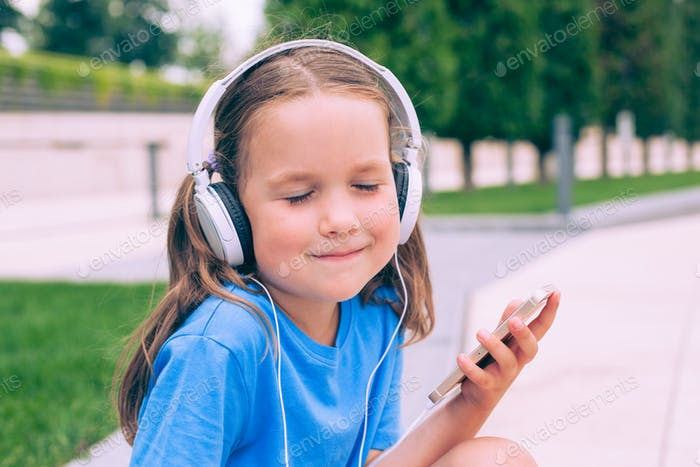 Cute little girl listening to music on the phone with headphones