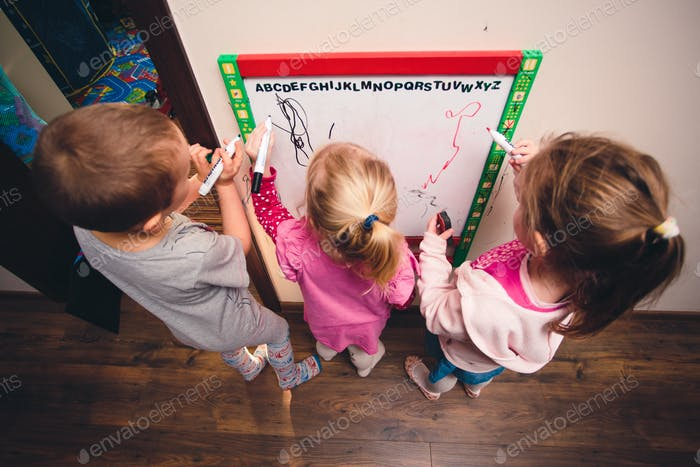 Children drawing a pictures learning a alphabet characters playing together using whiteboard and