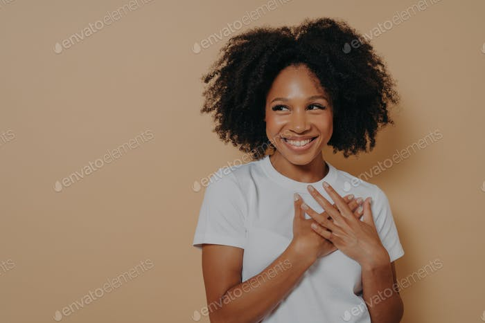 Portrait of happy african woman posing with smile looking away, holding hands on chest