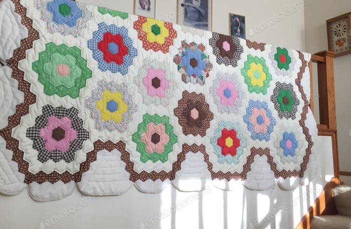 Grandmother's Flower Garden pattern on handmade quilt hanging over banister