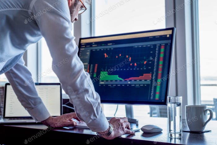 Man at desk looking at computer screen showing stock market trading data.