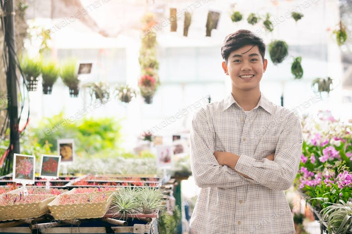 Confident young  owner small business orchids flower shop store.