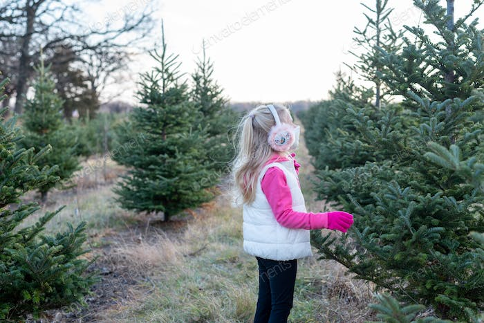 Little girl in fashionable earmuffs and face mask at the Christmas tree farm
