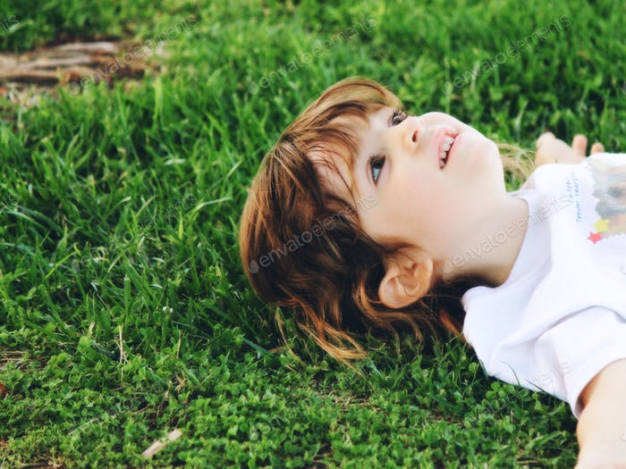 Girl on green grass in springtime.