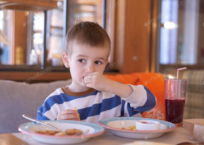 a little boy of European appearance eats  in a cafe