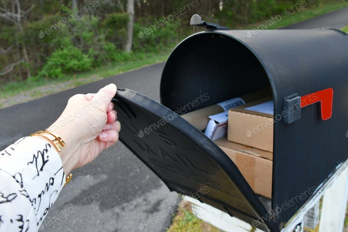 Opening a mailbox full of boxes packages delivered by the mailman USPS, generic brown box
