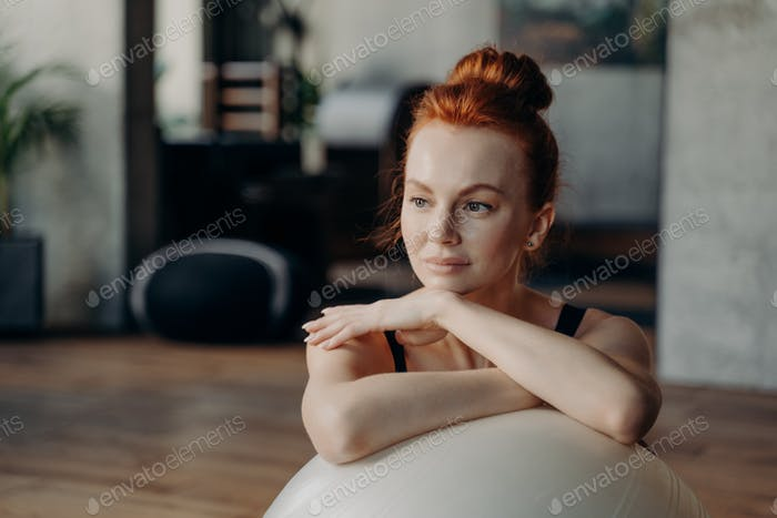 Close up of attractive woman leaning on fitball and looking aside