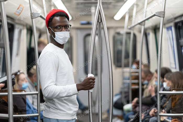Black millennial man wear face mask as protection against covid-19, holding handrail in subway train