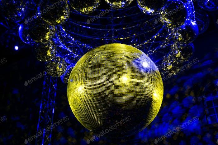 Goldene Discokugel auf einem dunkelblauen Hintergrund.