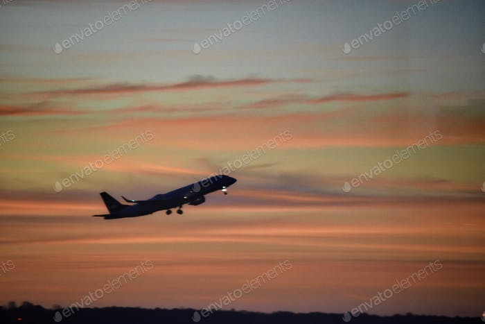 Plane taking off from Boston Logan airport right before sunset