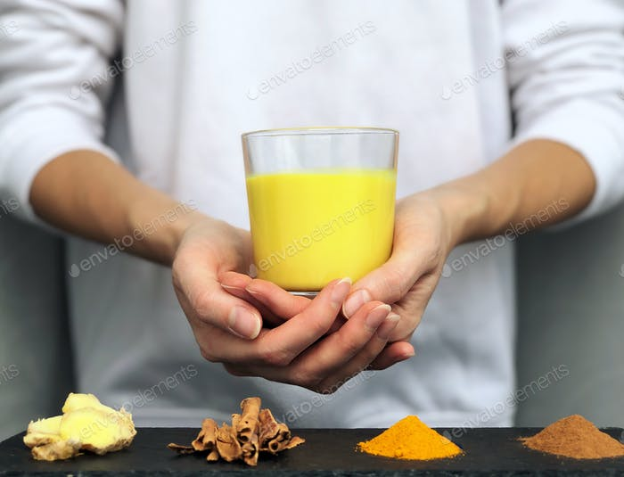 Hands holding a glass of golden milk (turmeric milk) - alternative medicine concept, naturopathy