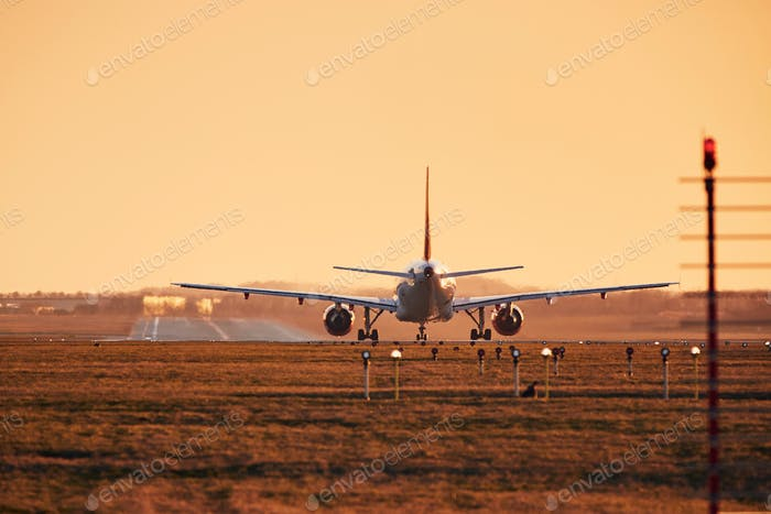 Airplane is on runway ready for take off. Traffic at airpot at sunset.