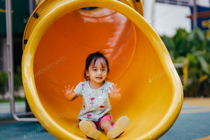 Toddler sittting at the end of the slide in the playground.